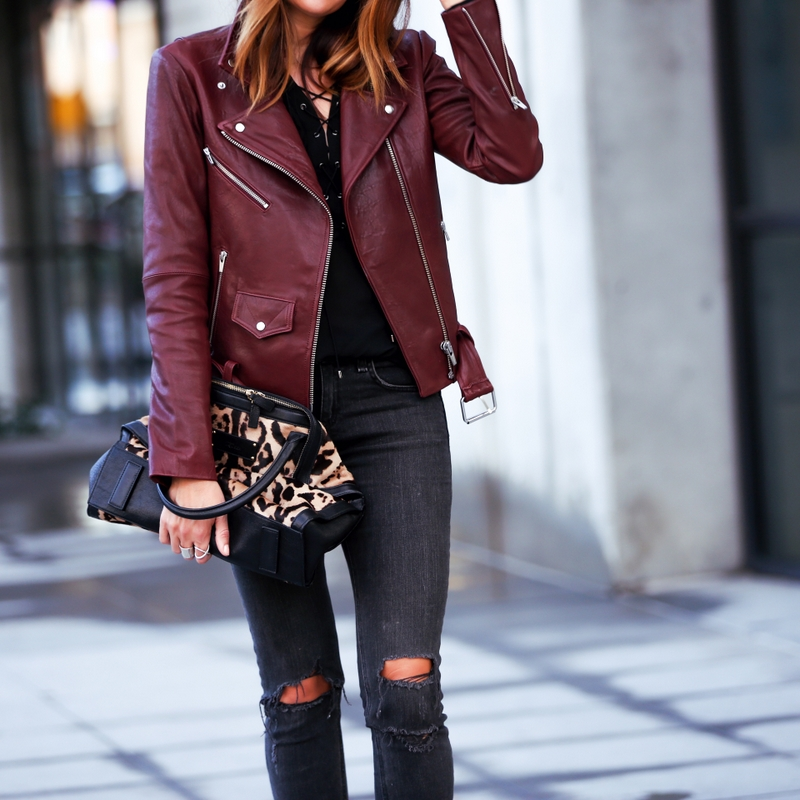 red leather jacket with lace up top and leopard print bag