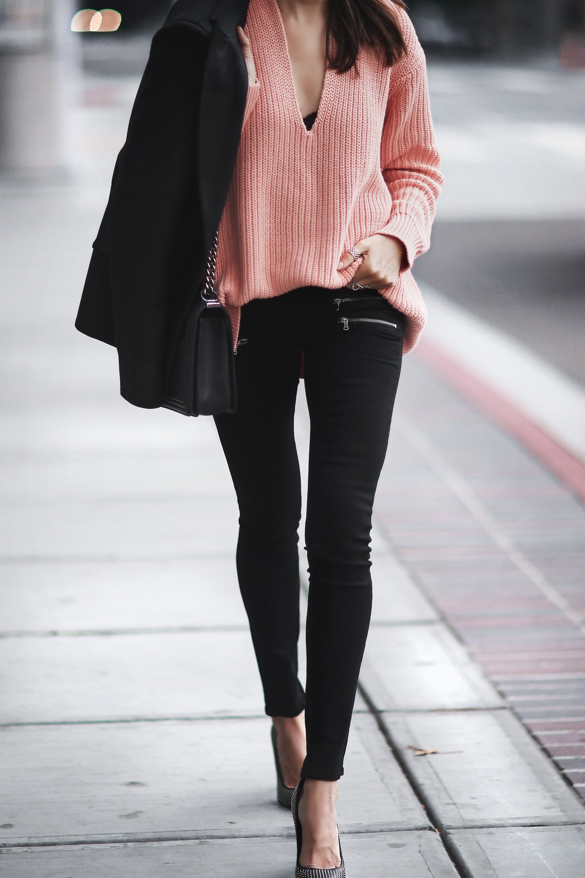 coral sweater, skinny jeans with zippers, black blazer, studded pumps