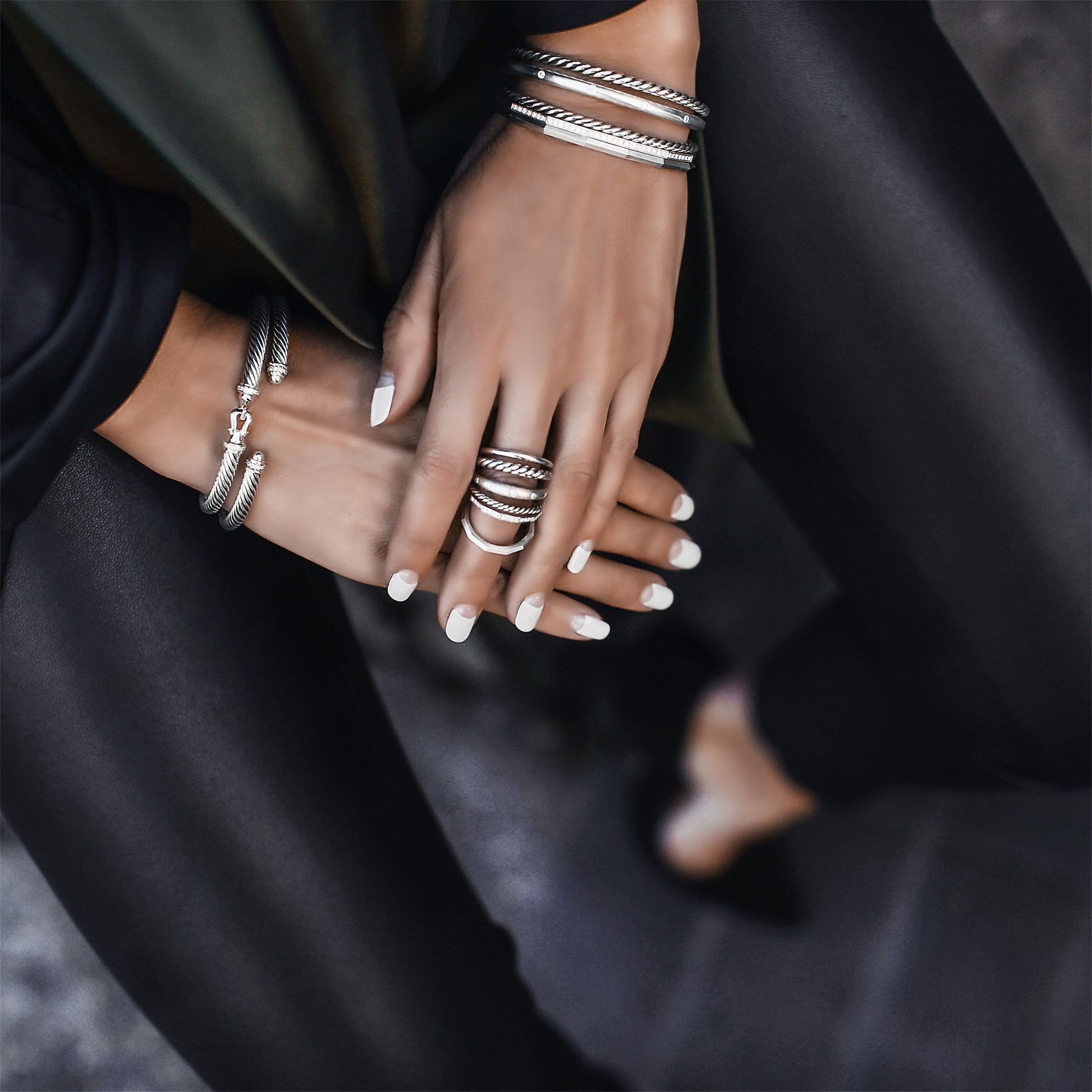 stacked silver rings and bracelets