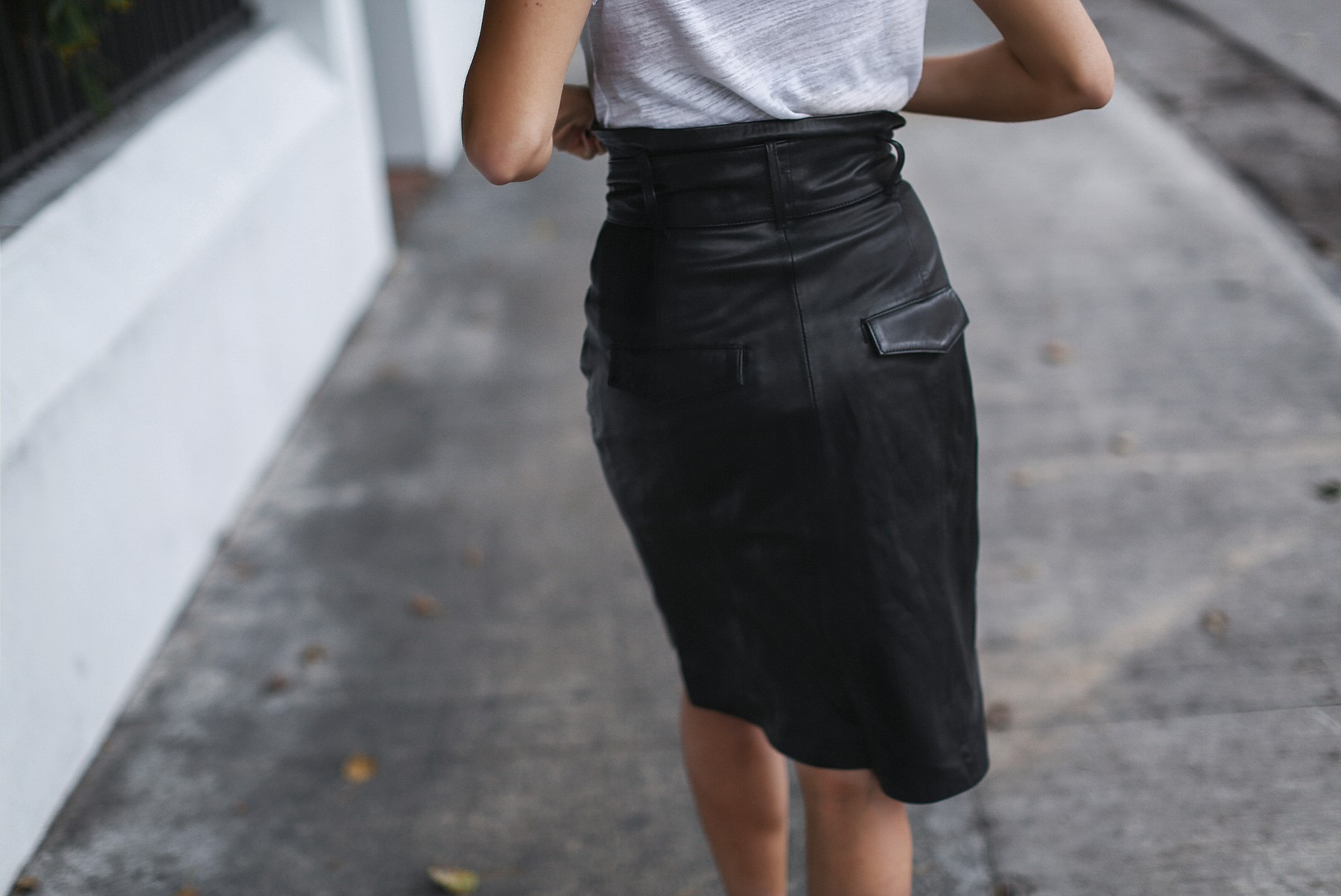 black knee length leather skirt with pockets and white tshirt