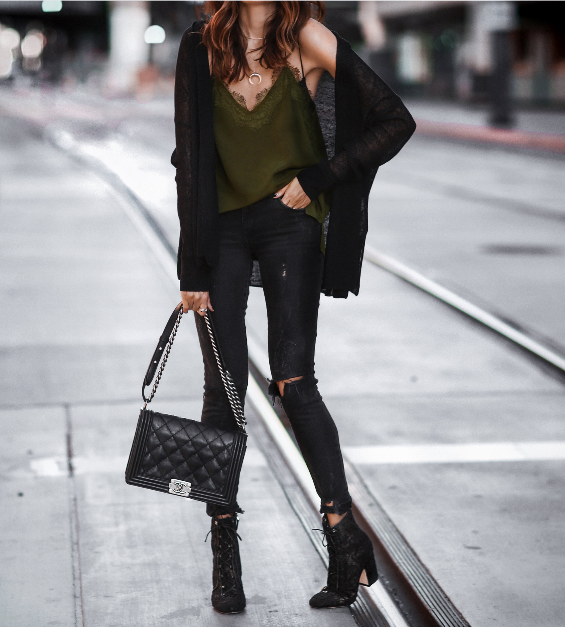 green lace cami, black cardigan, black ripped skinny jeans, chanel bag, black lace up booties
