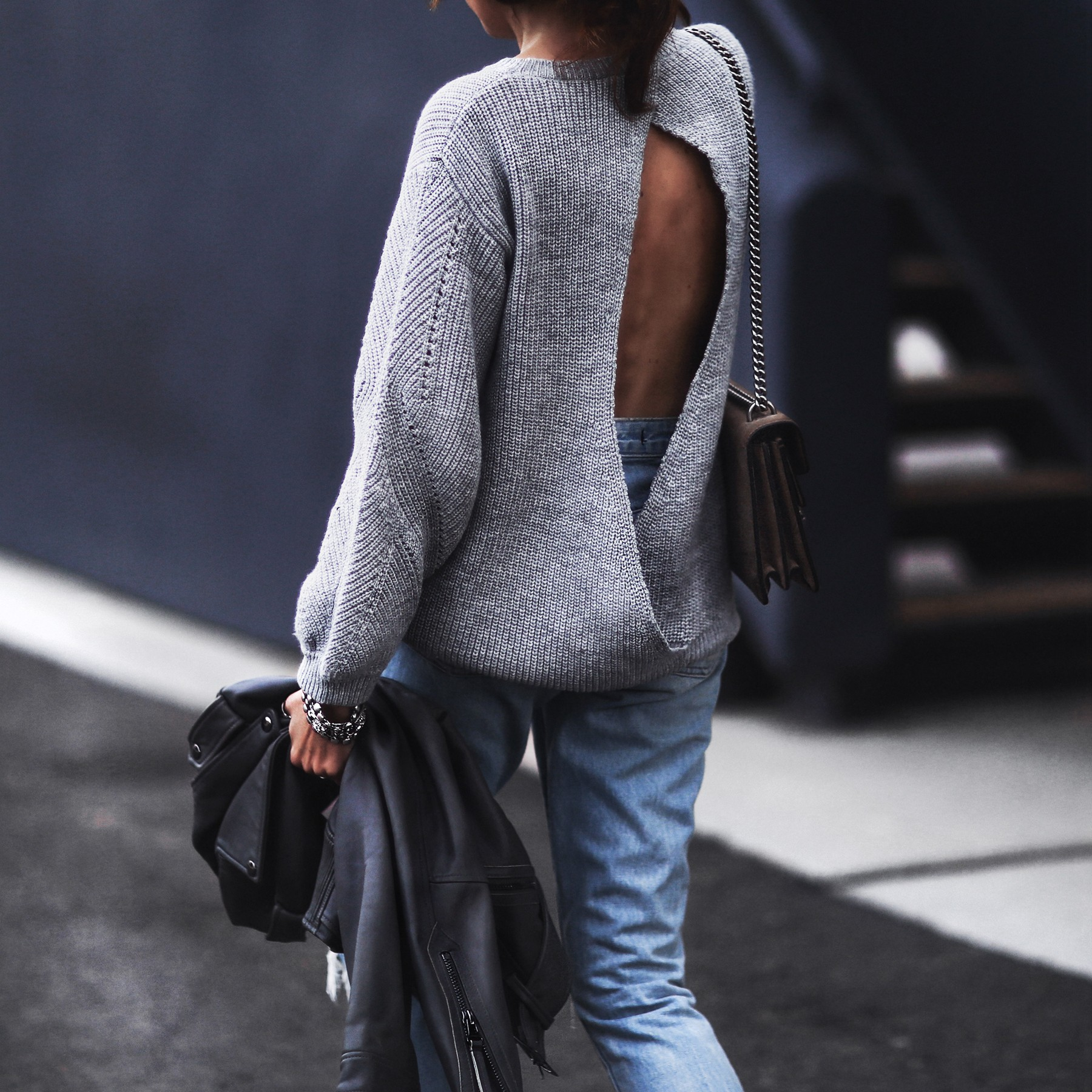 gray open back sweater, moto jacket, ripped boyfriend jeans, gucci bag