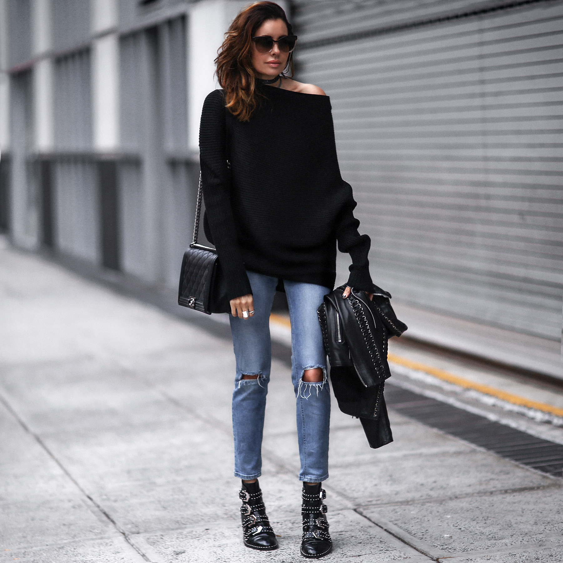 black off the shoulder sweater, ripped skinny jeans, black studded boots, black leather jacket, chanel bag
