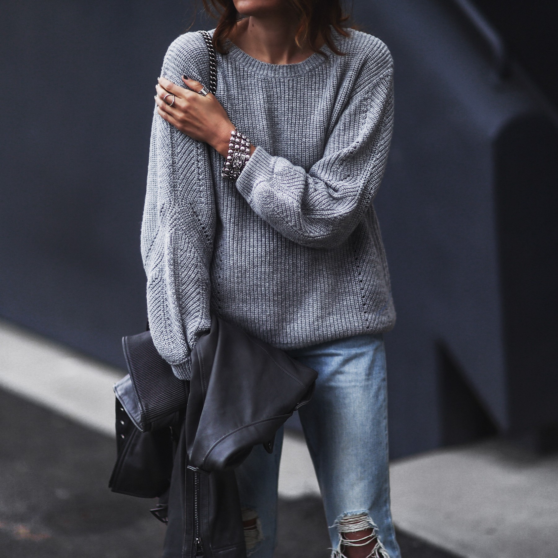 gray open back sweater, moto jacket, ripped boyfriend jeans