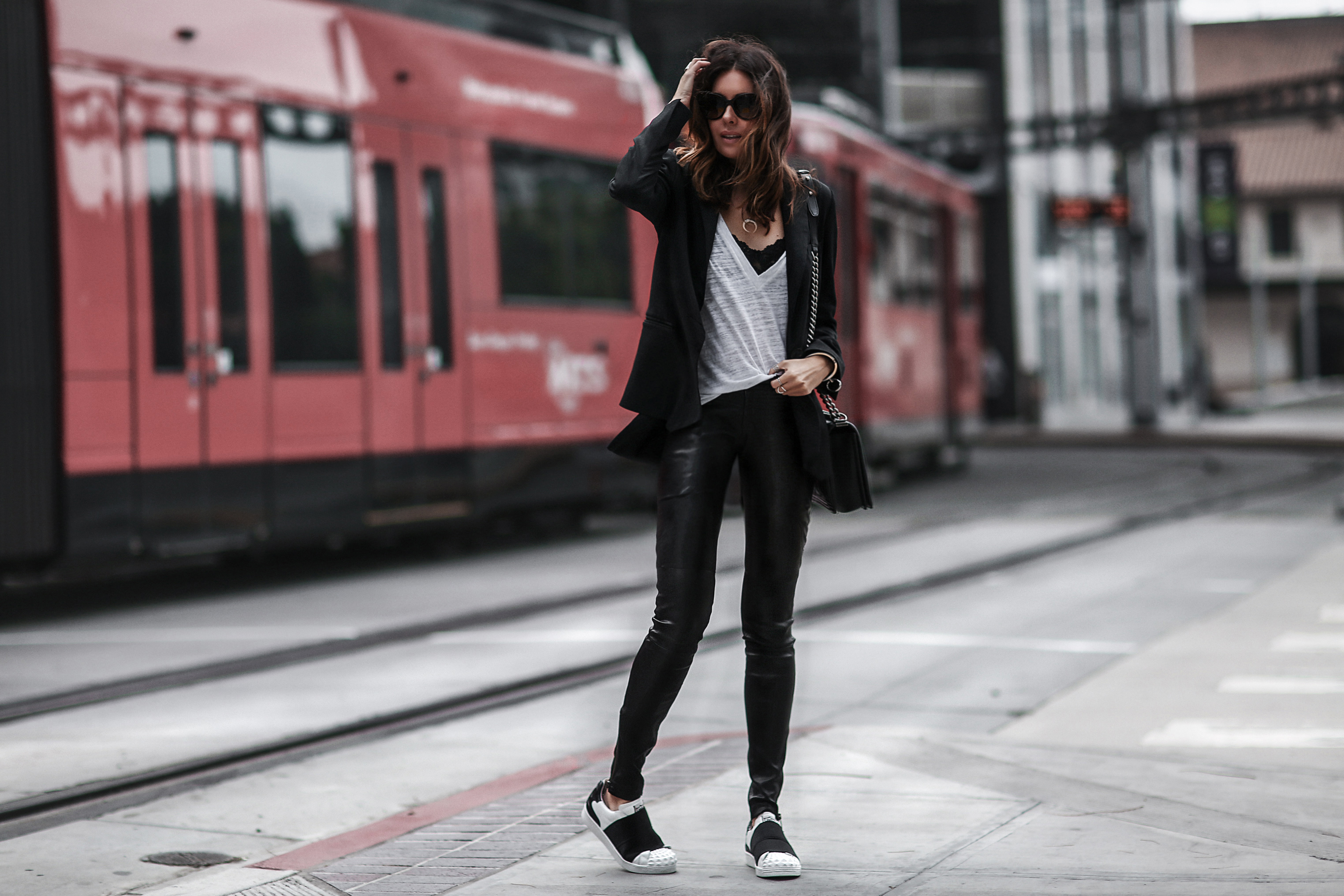 sneakers with elastic strap and studs, black leather pants, black blazer