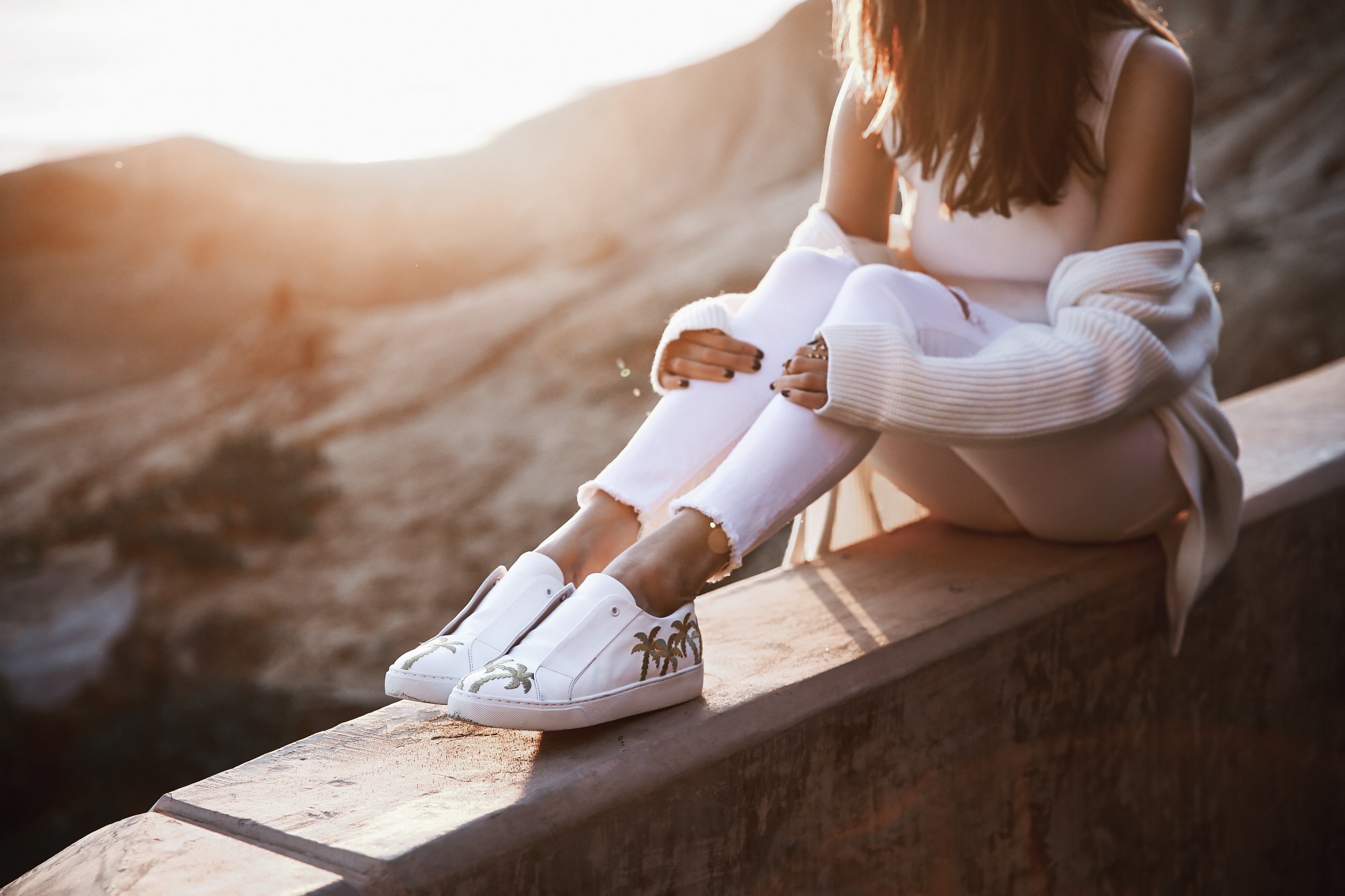 white sneakers with palm trees, white skinny jeans, white cardigan