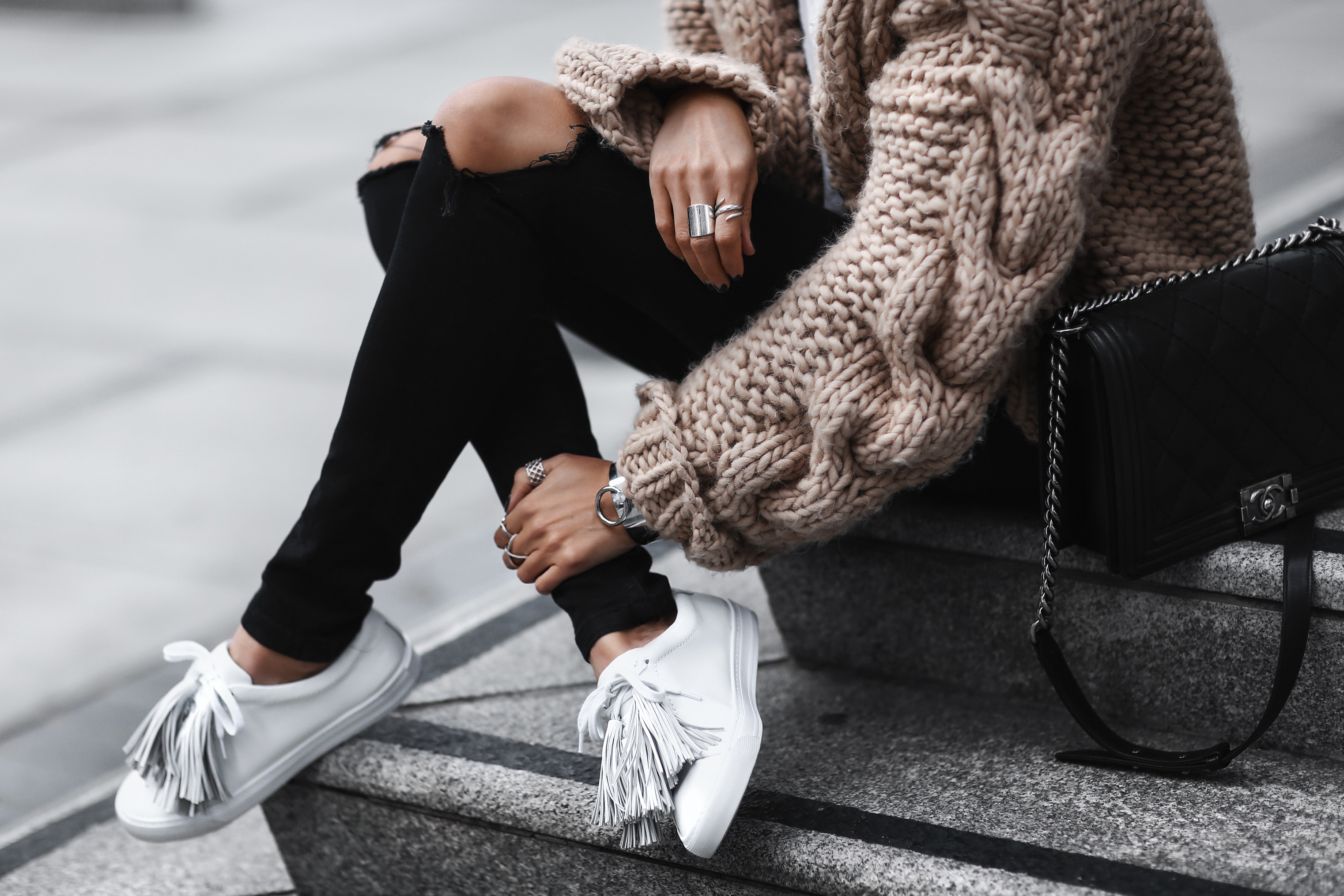 white sneakers with fringe, chunky cable knit sweater, black ripped skinny jeans, chanel bag