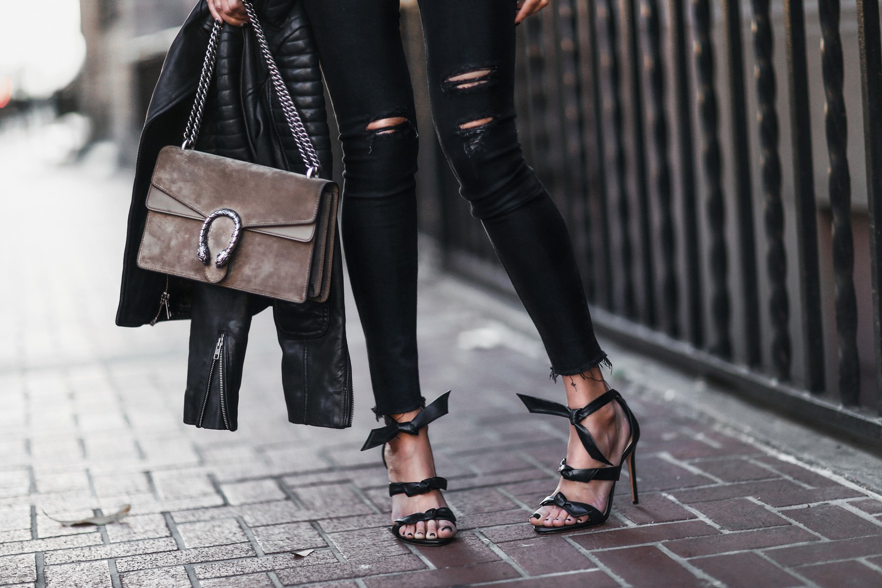 black ripped skinny jeans, black heels with bows, leather jacket, gucci bag