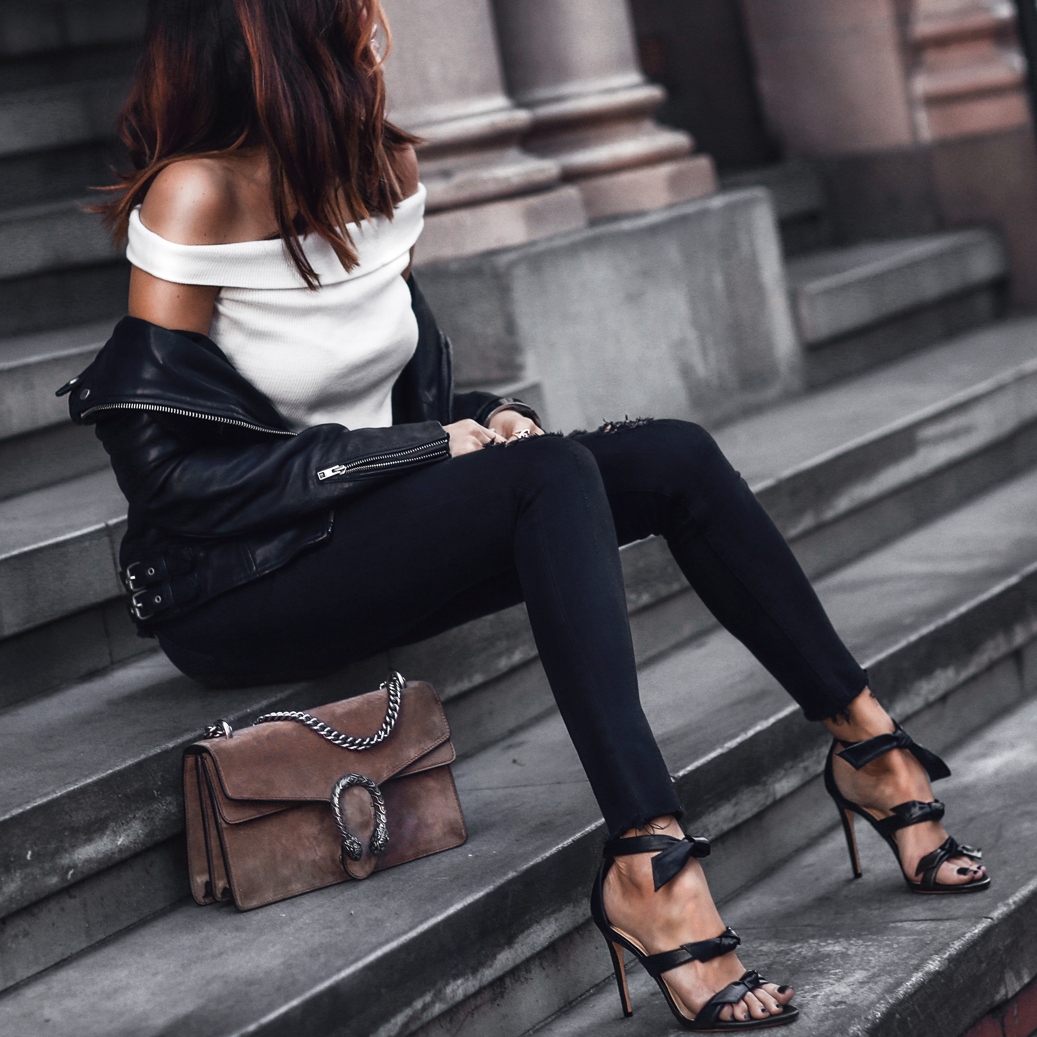 off the shoulder top, black leather jacket, ripped skinny jeans, black heels with bows, gucci bag
