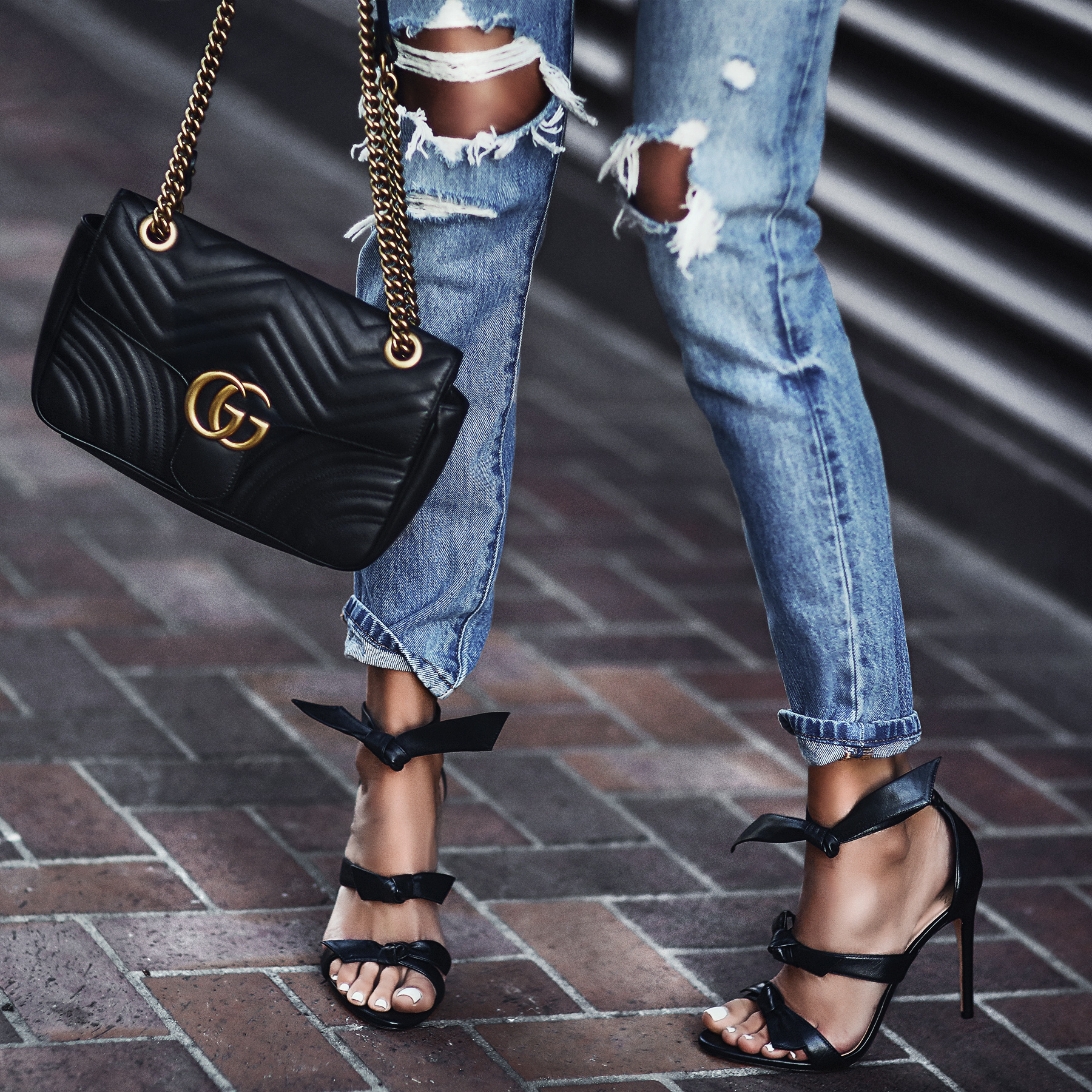 ripped levi's, black heels with bows, gucci bag