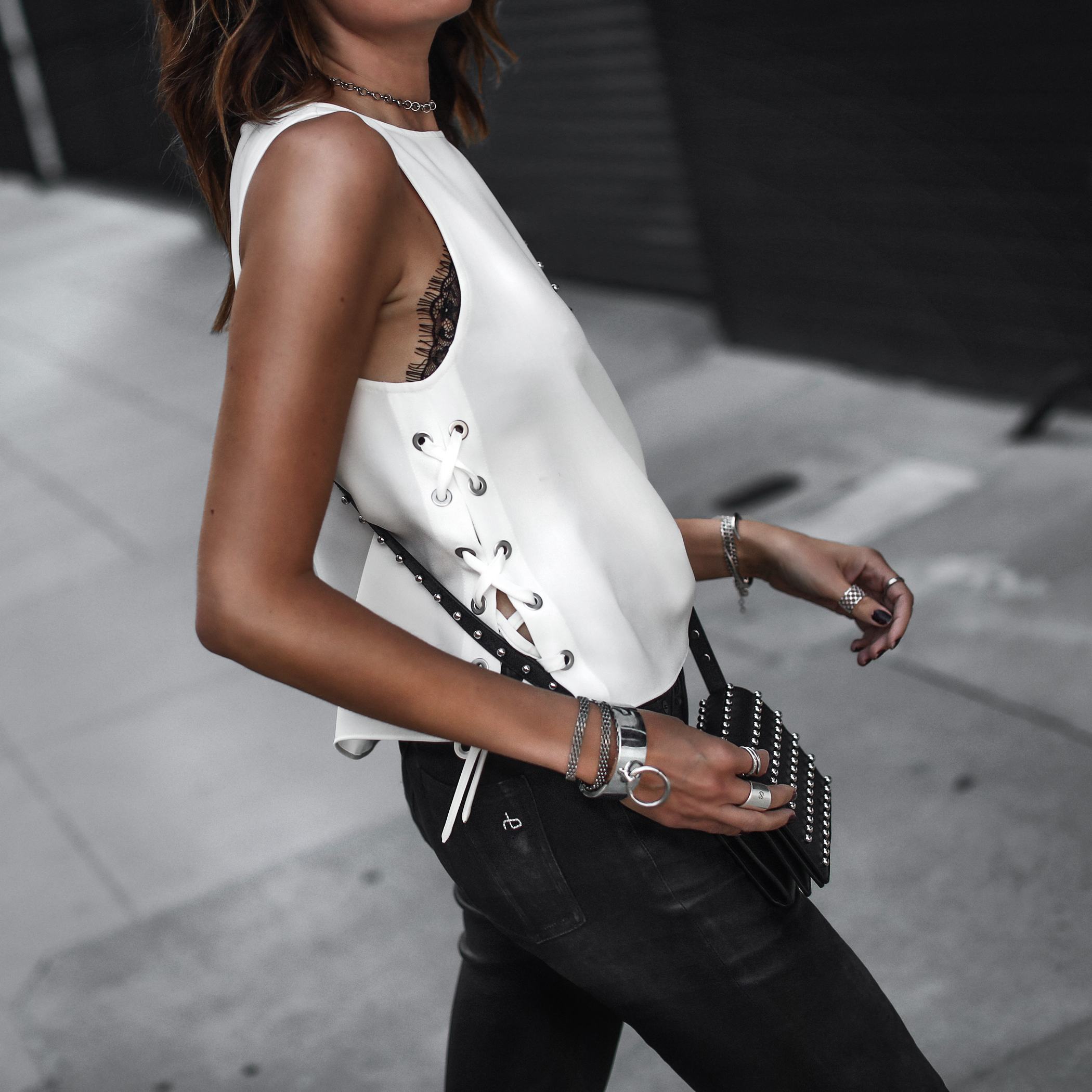 lace-up tank top, black leather pants, studded crossbody bag, lace bralette