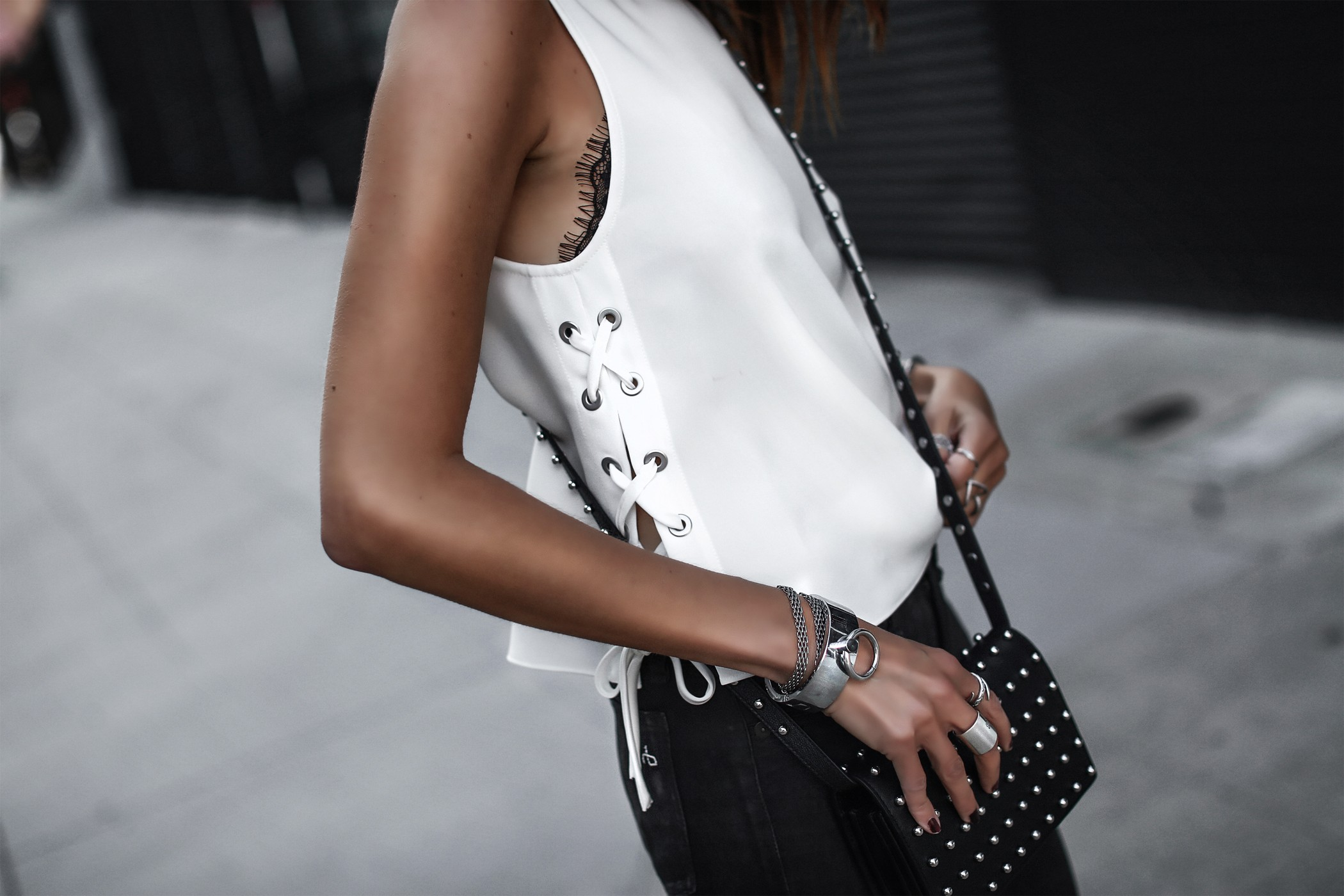 lace-up tank top, black leather pants, studded crossbody bag