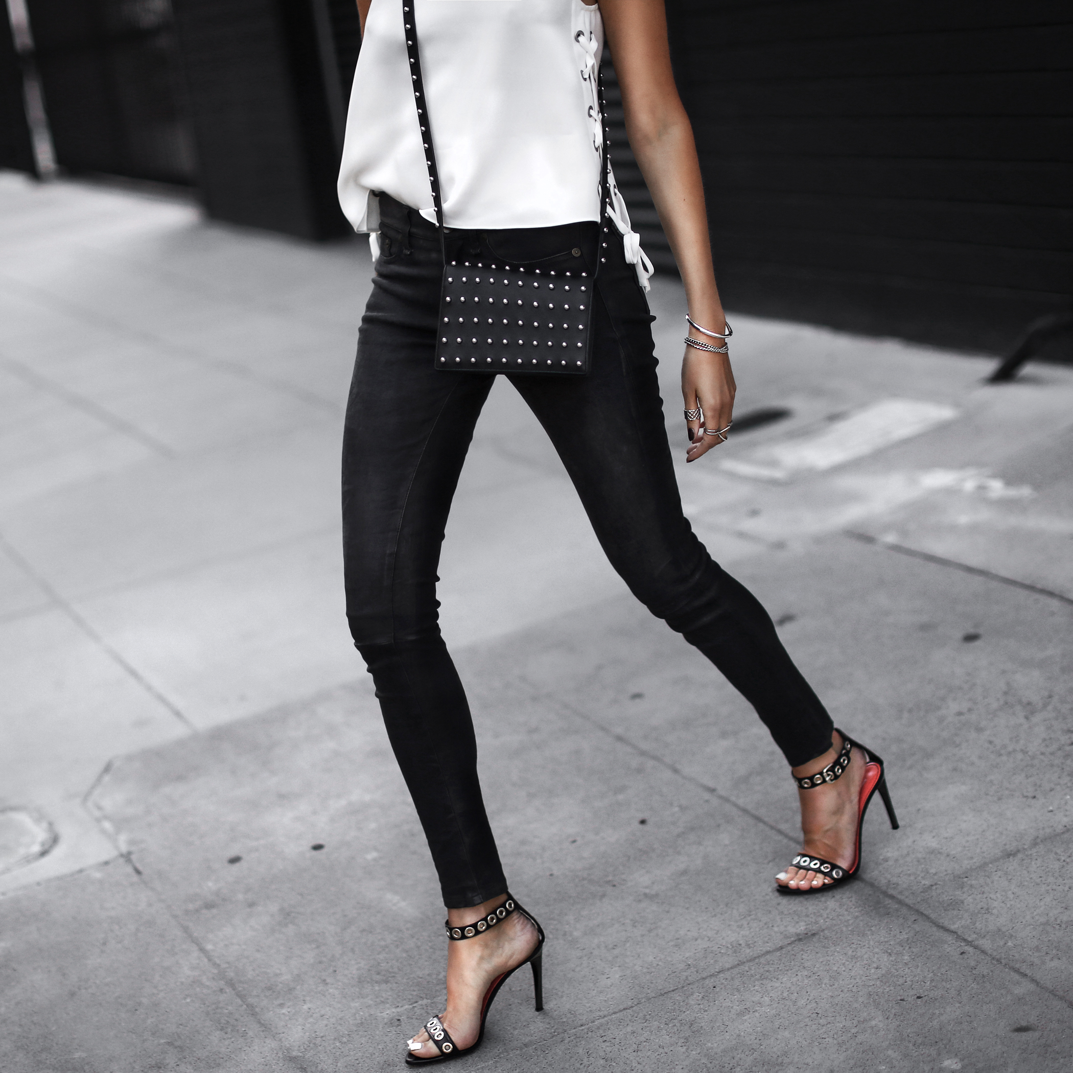 lace-up tank top, black leather pants, studded crossbody bag, black studded sandals