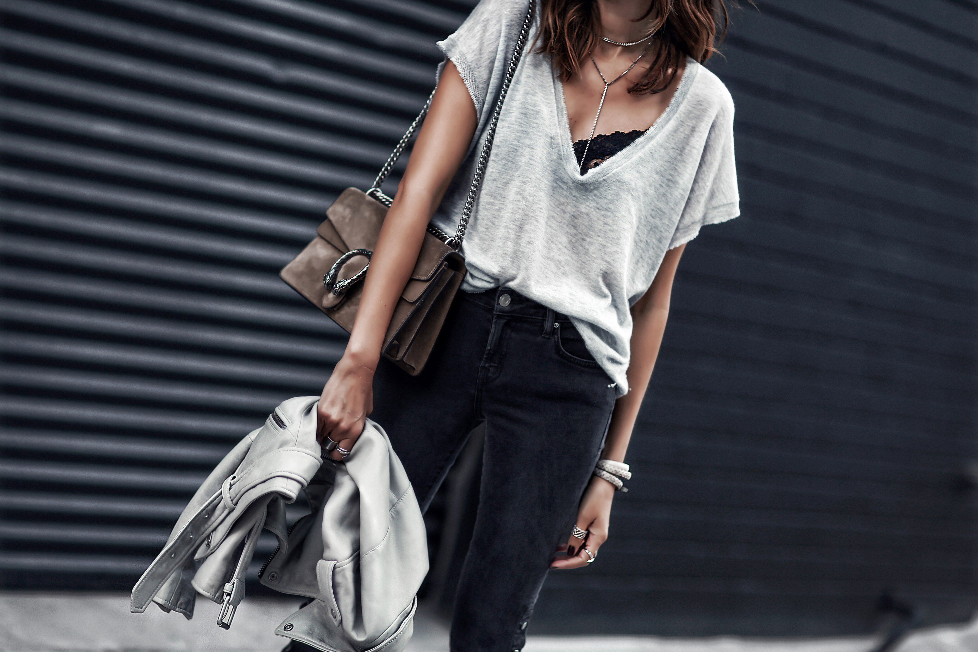 gray oversized knit tshirt, black lace bralette, faded black jeans with snaps, gray leather jacket, gucci bag