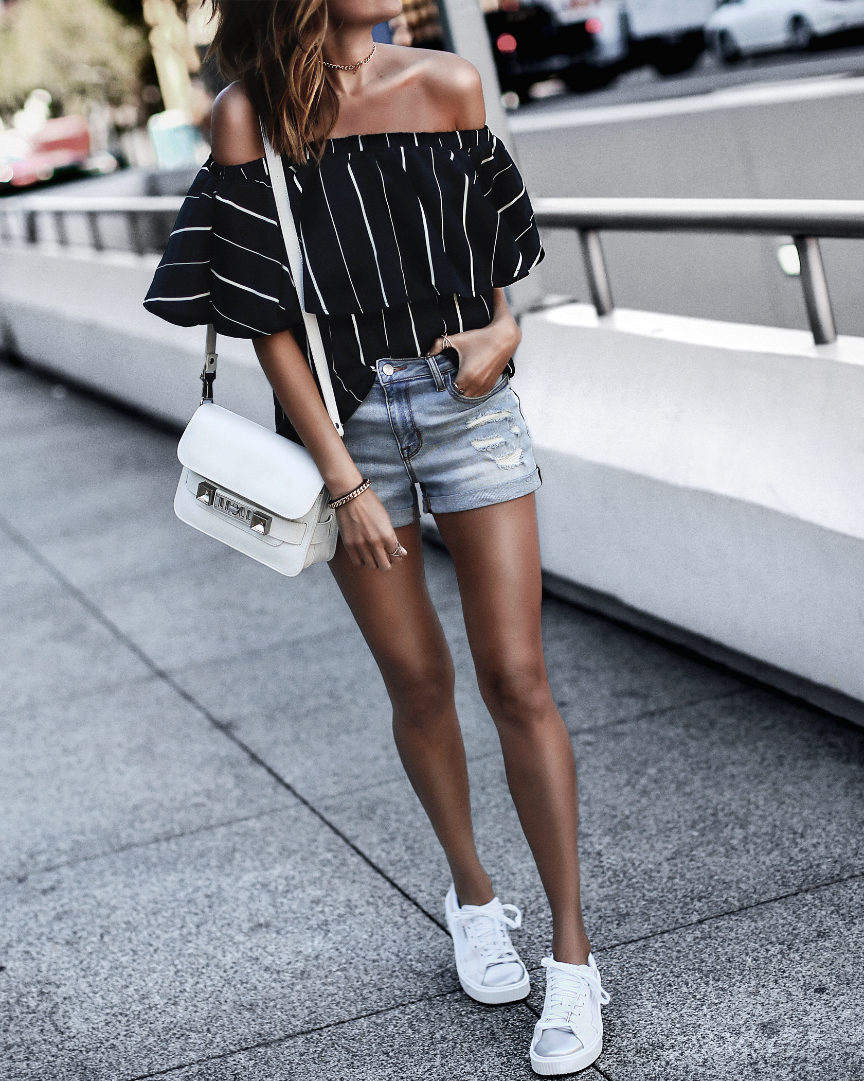 off the shoulder striped top, ripped light wash jean shorts, puma sneakers