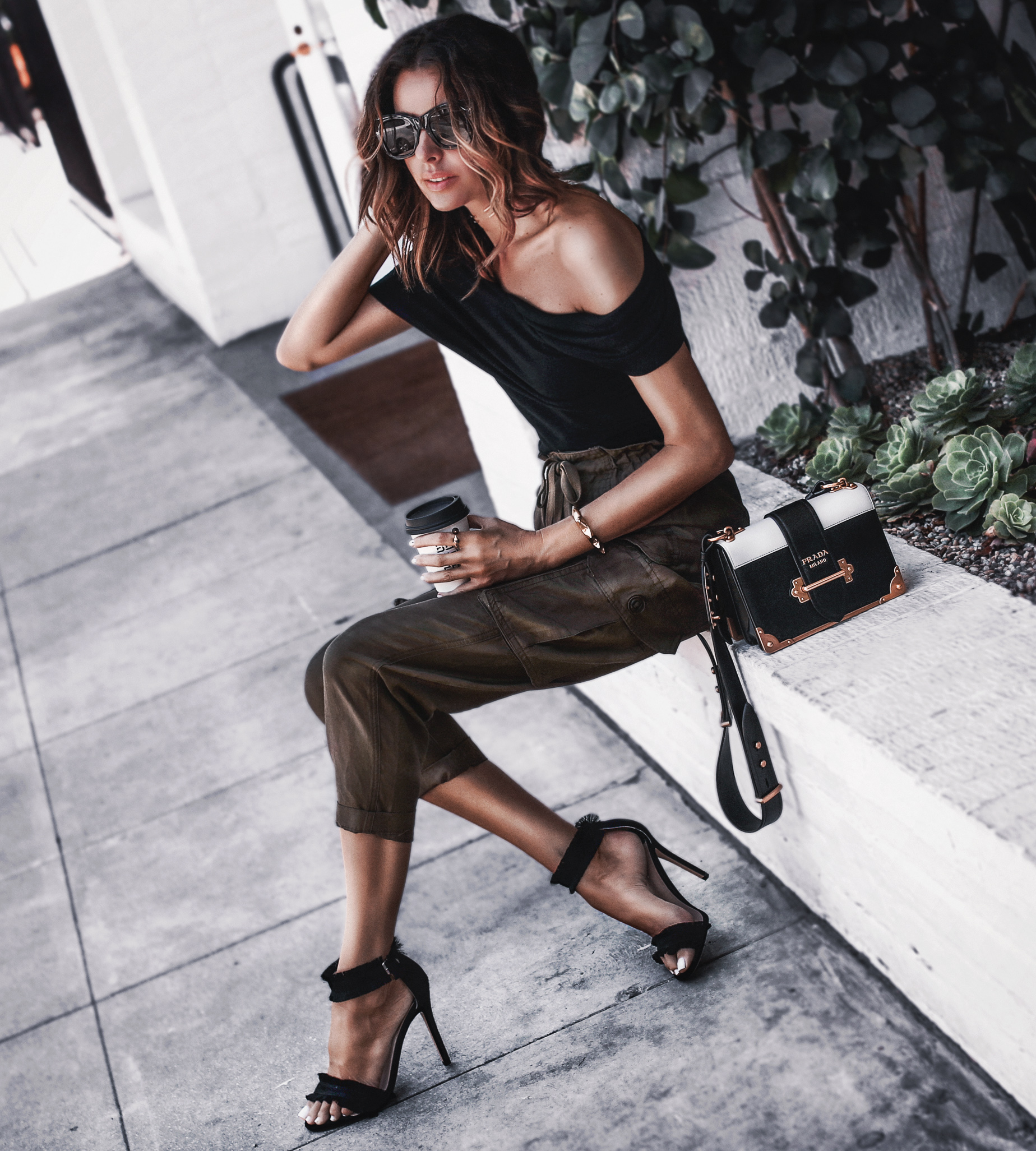 black off the shoulder top, olive green cargo pants, black frayed sandals, prada bag