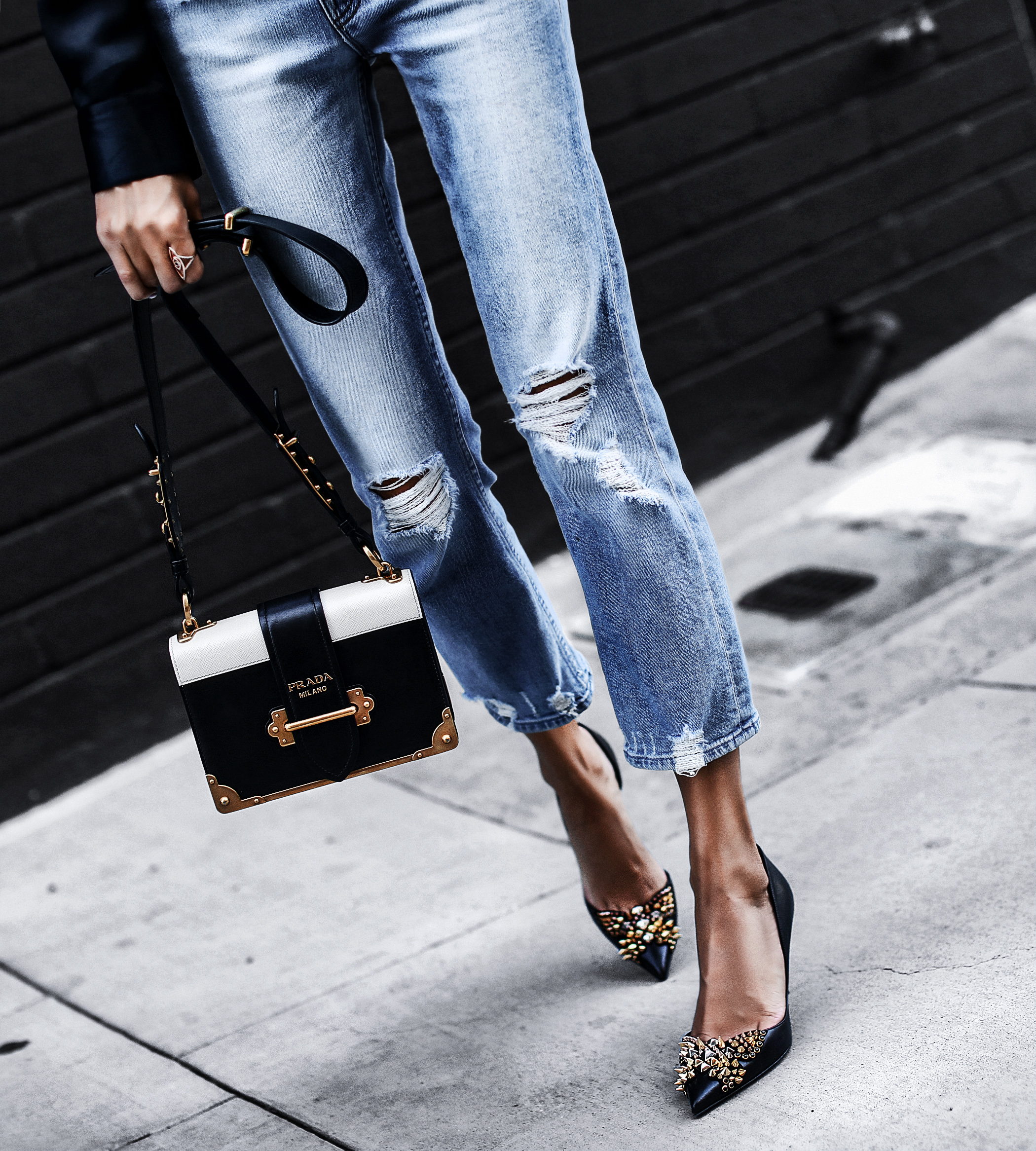 distressed light wash mom jeans, prada bag, black pointed heels with gold spikes