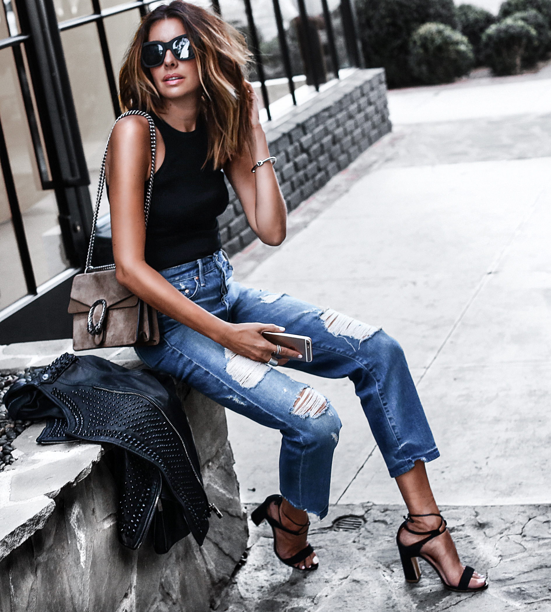 black tank, ripped mom jeans, black sandals, studded leather jacket, gucci bag